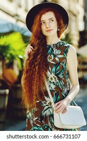 Outdoor portrait of young beautiful happy redhead girl with freckles, long curly hair. Model posing in street, looking up, carrying crossbody bag, wearing dress. Female natural beauty, fashion concept