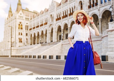 Outdoor portrait of young beautiful happy smiling girl posing in street of old european city. Model wearing stylish white, blue clothes, straw hat. Copy, empty space for text