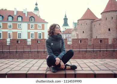 Outdoor portrait of young beautiful lady posing on old street. Evening old Warsaw, Poland, spring