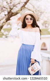Outdoor portrait of young beautiful lady wearing stylish round sunglasses, straw hat, off shoulder blouse, pleated blue skirt, holding small white bag, posing in street. Spring, summer fashion concept