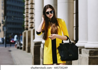 Outdoor portrait of young beautiful lady walking on the street. Model wearing sunglasses & stylish yellow summer dress. Girl looking down. Female fashion concept. City lifestyle. Sunny day. Waist up
