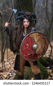 Outdoor portrait of young beautiful viking woman warrior with blue eyes wearing ram horns holding ax and shield looking threatening. Female Viking on forest with specific makeup and fur collar