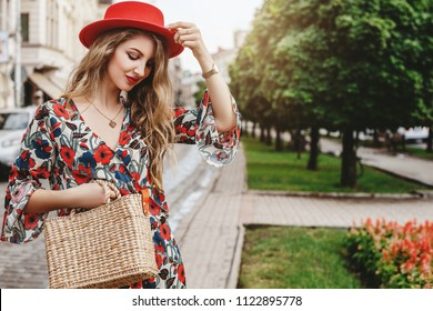 Outdoor portrait of young beautiful woman wearing stylish jumpsuit with floral print, red hat, wrist watch, necklace, holding straw bag. Model posing in street of european city. Copy space for text