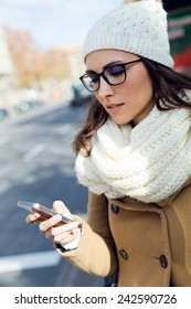 Outdoor portrait of young beautiful woman using her mobile phone