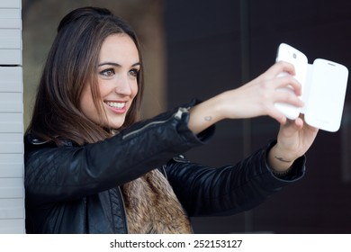 Outdoor portrait of young beautiful woman taking a selfie in the street.