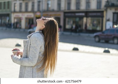 Outdoor portrait of young beautiful woman with long hair , coffee to go and sunglasses, looking at the sky