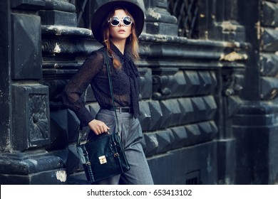 Outdoor portrait of young beautiful woman, businesswoman posing in street, european city. Model wearing stylish clothes, glasses, hat, holding bag. Female fashion concept. Copy, empty space for text