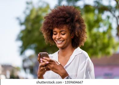 Außenporträt einer jungen schwarzen Afroamerikanerin, die auf dem Handy spricht