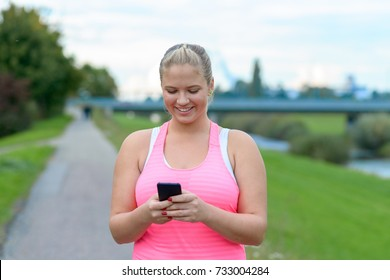 Outdoor portrait of young blonde smiling woman using mobile phone