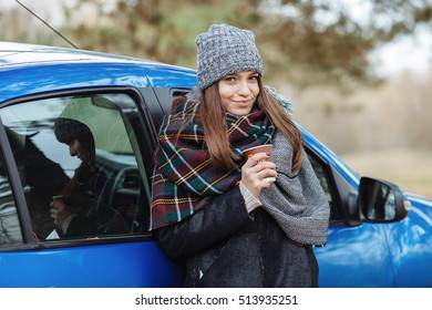 Outdoor portrait of young caucasian woman, holding a cup of takeaway coffee in forest park on cold season day. Dressed in an elegant leather jacket, grey hat and big cozy scarf