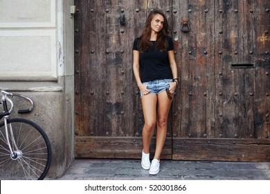 An outdoor portrait of a young cute hipster girl wearing black blank t-shirt and blue jeans shorts with a fixed gear bike while standing on the wooden door background. Empty space for text or design.