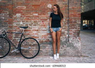 An outdoor portrait of a young cute student girl wearing black blank t-shirt and blue jeans shorts with a fixed gear bicycle while standing on the brick wall background. Empty space for text or design