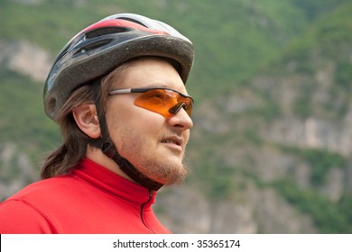 Outdoor portrait of a young cyclist in helmet and sunglasses, observing the mountain scenery