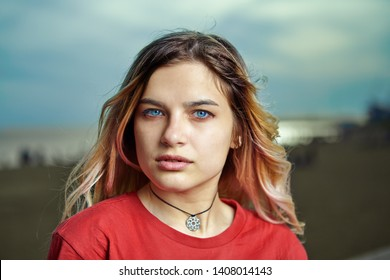 Outdoor portrait of young european woman about 20 years old with blond hair and red T-shirt, close-up.