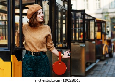 Outdoor portrait of young fashionable woman wearing beige beret, turtleneck, green corduroy trousers, belt, holding round orange suede handbag, posing in street of european city. Copy space for text