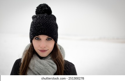 Outdoor portrait of a young girl in winter hat with pom-pom scarf and snowy plains in the background