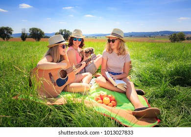 Outdoor portrait of young girls with a guitar