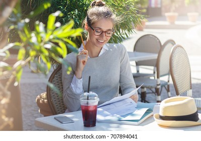 Outdoor portrait of young good-looking Caucasian female in glasses sitting at cafe table outdoors and filling in forms on papers with pencils feeling happy about both working and having nice rest