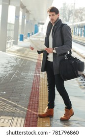 outdoor portrait of young handsome man standing at train station holding map in hands wearing warm coat