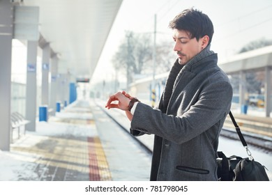 outdoor portrait of young handsome man standing at train station checking time wearing warm coat