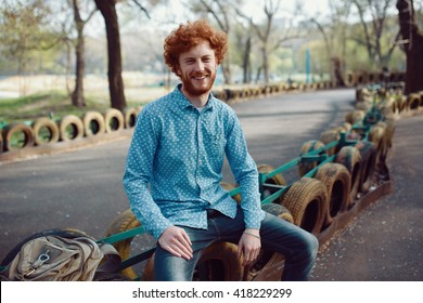 Outdoor portrait of young handsome smiling ginger man with beard