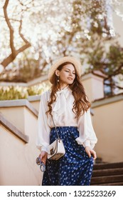 Outdoor portrait of young happy beautiful fashionable lady posing in spring city. Model wearing straw hat, stylish blouse, blue skirt, carrying small shoulder bag.