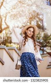 Outdoor portrait of young happy beautiful fashionable lady posing in spring city. Model wearing straw hat, stylish white blouse, blue skirt, carrying small shoulder bag. Sunny day light