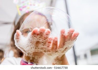 outdoor portrait of young happy child playing with soap bubbles on natural background