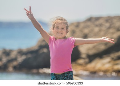 outdoor portrait of young happy smiling child girl playing run on beach