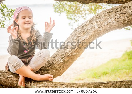 outdoor portrait of young happy smiling child girl meditating on natural background