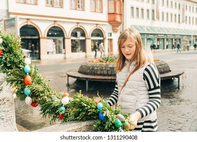 Outdoor portrait of young kid girl playing with easter decoration on the streets of old european city