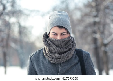 outdoor portrait of young  man freezing in hat wearing coat posing on the street