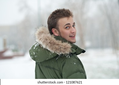 outdoor portrait of young man in green winter jacket
