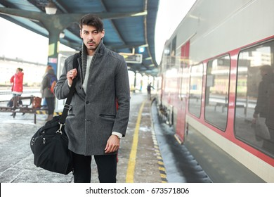 outdoor portrait of young man standing next to the train carrying duffle bag