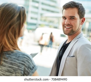 Outdoor portrait of young man standing on the street, talking to friend.
