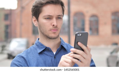 Outdoor Portrait of Young Man Using Smartphone