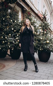 Outdoor portrait of young positive smiling blondie girl in black coat walking along the christmas decorations in the city streets