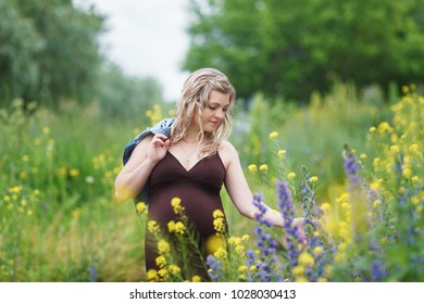 Outdoor portrait of young pregnant woman in the field. beautiful pregnant woman  relaxing in the summer nature meadow. pregnant woman relaxing in flowers