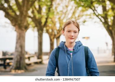 Outdoor portrait of young preteen girl wearing backpack, listeming music with earphones
