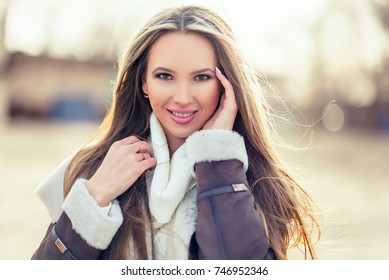 Outdoor portrait of young pretty beautiful woman in cold sunny winter weather in park. Sensual blonde posing and having fun