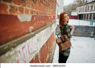 An outdoor portrait of a young pretty girl with red hair wearing checkered dress with girly backpacks standing on the brick wall background in winter day.