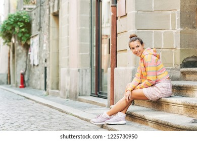 Outdoor portrait of young pretty woman sitting on steps in the city, wearing pink and yellow stripe sweatshirt, skirt, comfy purple sneakers