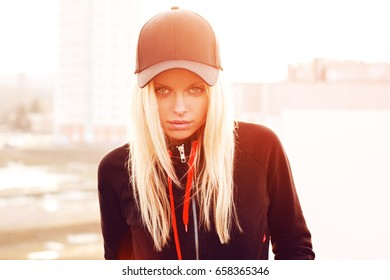 Outdoor portrait of young sensual woman in the cap closeup.
