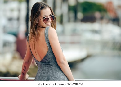 Outdoor portrait of young sexy tanned pretty woman standing on the pier near the sea marina. Back view of sensual girl in sunglasses