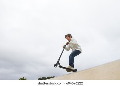 outdoor portrait of young teen boy riding a scooter on natural background