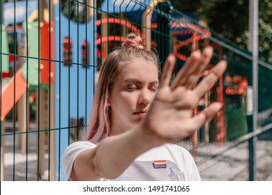 Outdoor portrait of young teenager hipster girl with pink hair and lgbt sign. young woman with LGBT rainbow sign shows stop sign with hands. LGBTQ youth, lgbt gay pride tolerance concept.
