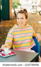 Outdoor portrait of young woman, drinking coffee in cafe, wearing yellow and pink stripes sweatshirt