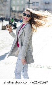Outdoor portrait of young woman with long flying blonde hair with coffee to go