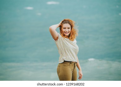 Outdoor portrait of young woman next to storm lake on a windy day