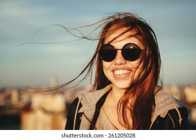 Outdoor portrait of young woman in round sunglasses having fun outdoor in summer in the city